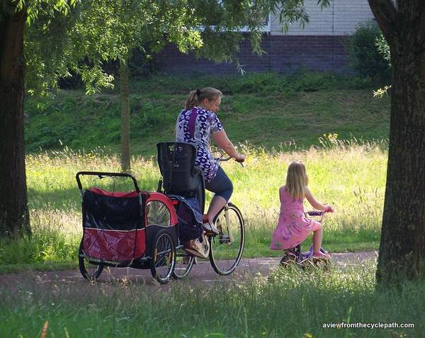 Mother cycling with daughter and with child-carry trailer behind